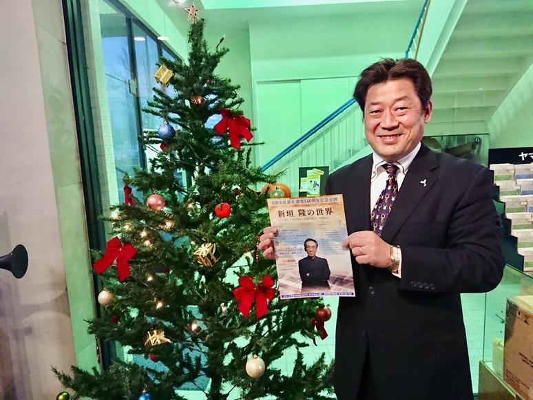 ポスターを持ちほほ笑む富永文喜新社長