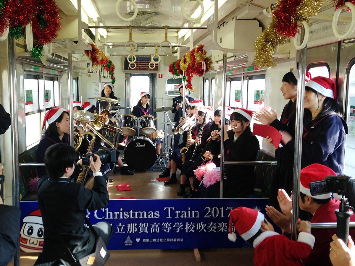 クリスマス仕様に装飾された列車内で演奏する那賀高校吹奏楽部