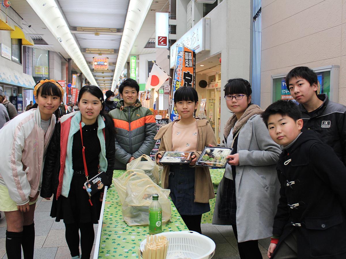 商店街でオリジナル弁当を販売した有功小学校6年2組の児童と担任の山八亮祐さん(左から3人目)