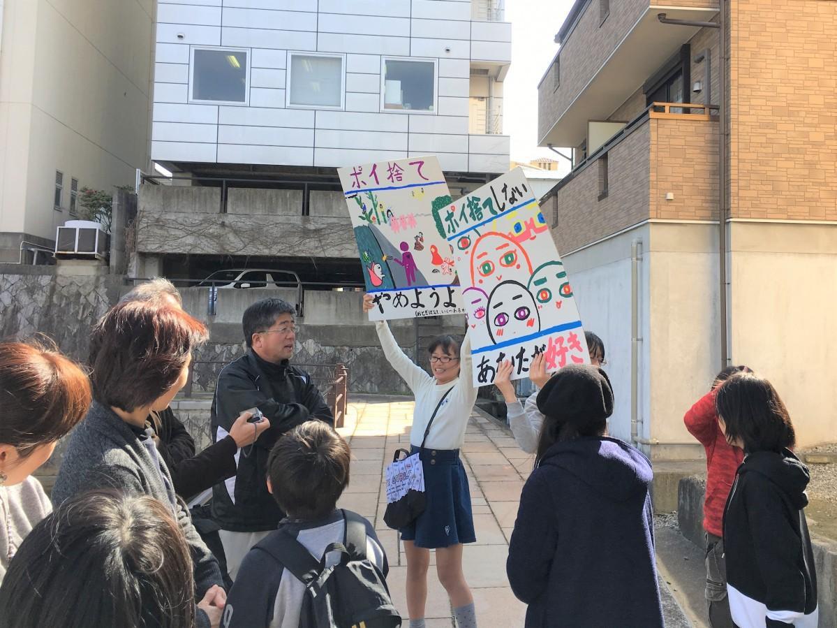 今回の活動を通して作成したポスターを掲げて川のゴミについて訴える