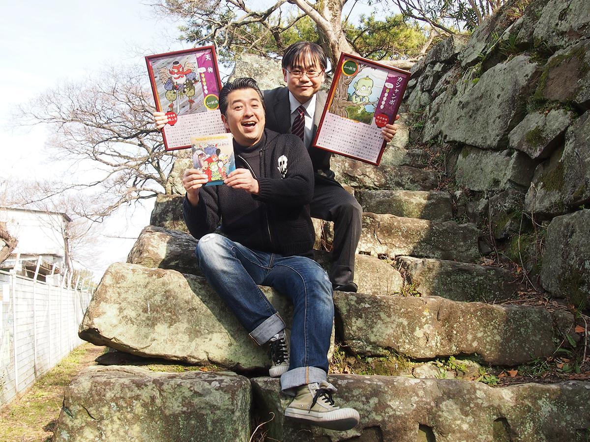 てんぐの出没スポット・和歌山城で書籍を手にするマエオカテツヤさん(左)と西山編集長