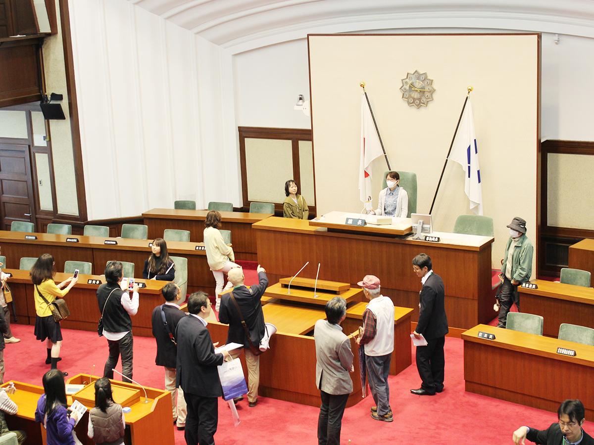 議長席に座って写真撮影する参加者たち