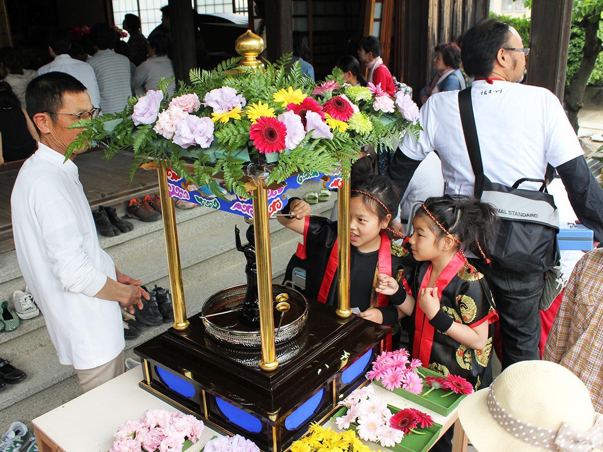昨年の花まつりの様子。花御堂の誕生仏に甘茶を注ぎ、釈尊の誕生を祝う