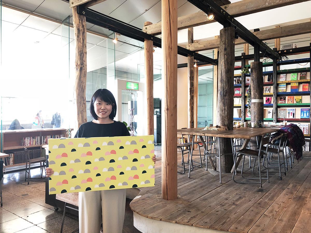 島塚絵里さんデザインの布を手にする武田さん