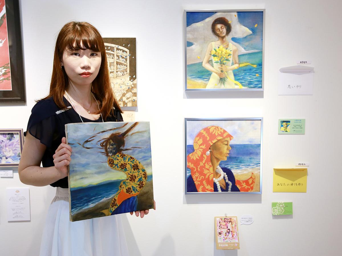 グループ展に出展した作品の隣で、新作を手にする小野明日香さん