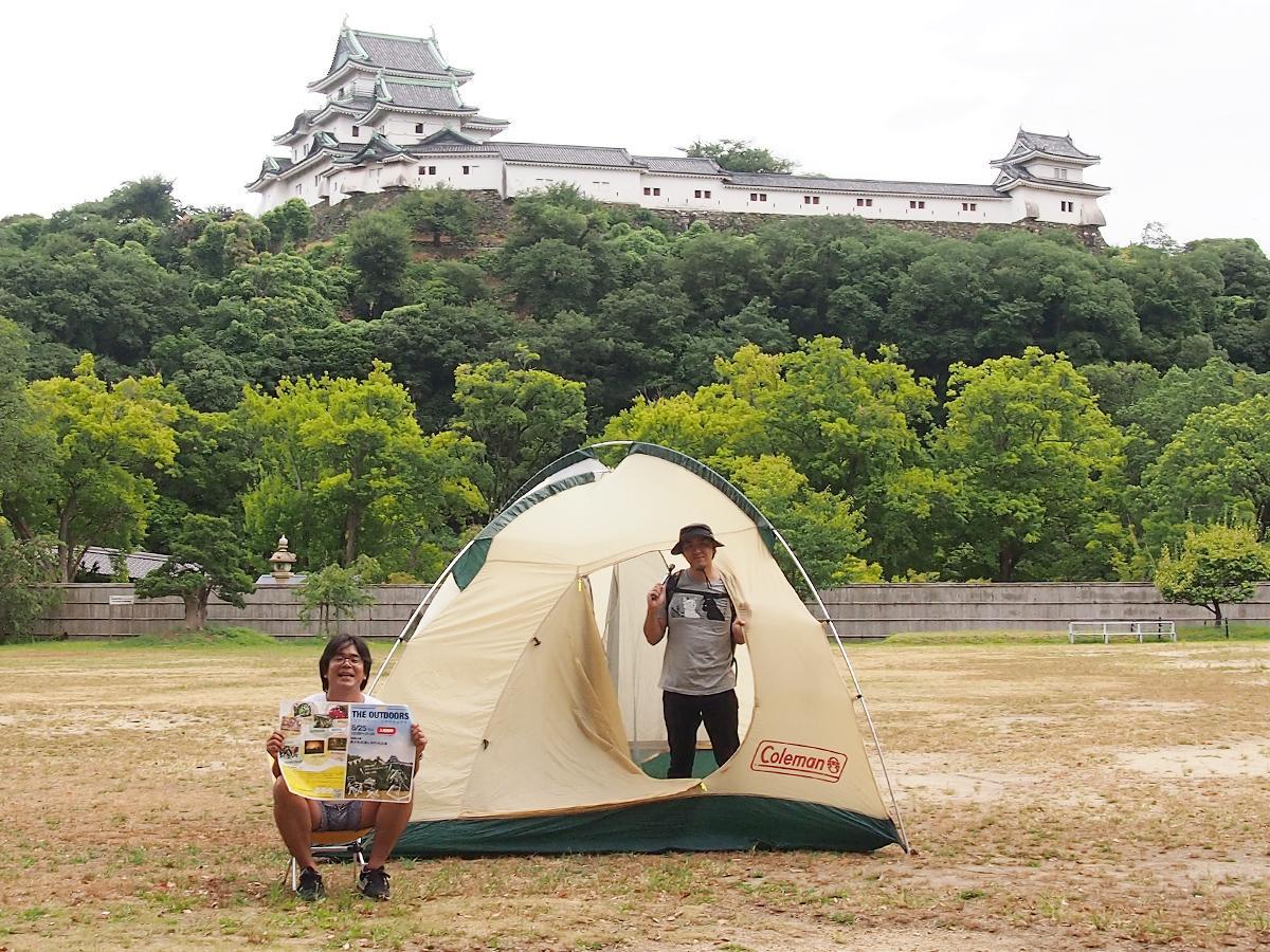 和歌山城西の丸広場でテントを広げる田中隆介さん(左)と小川貴央さん