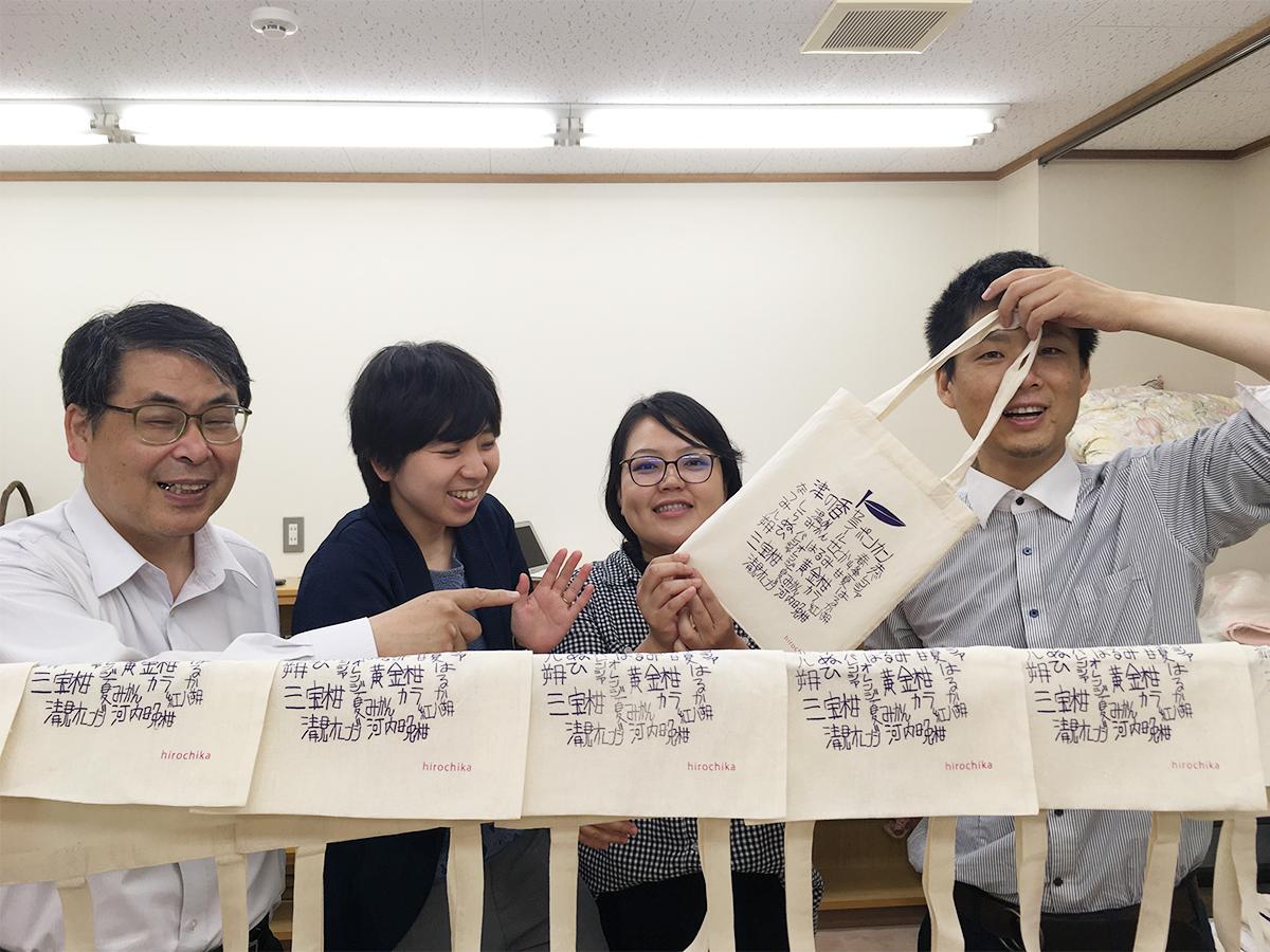 完成した「hirochikaバッグ」を手にする製作メンバー