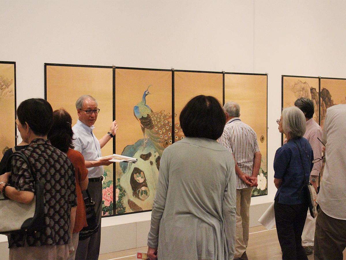 フロアレクチャーで黒住章堂のふすま絵の説明を聞く観覧者たち