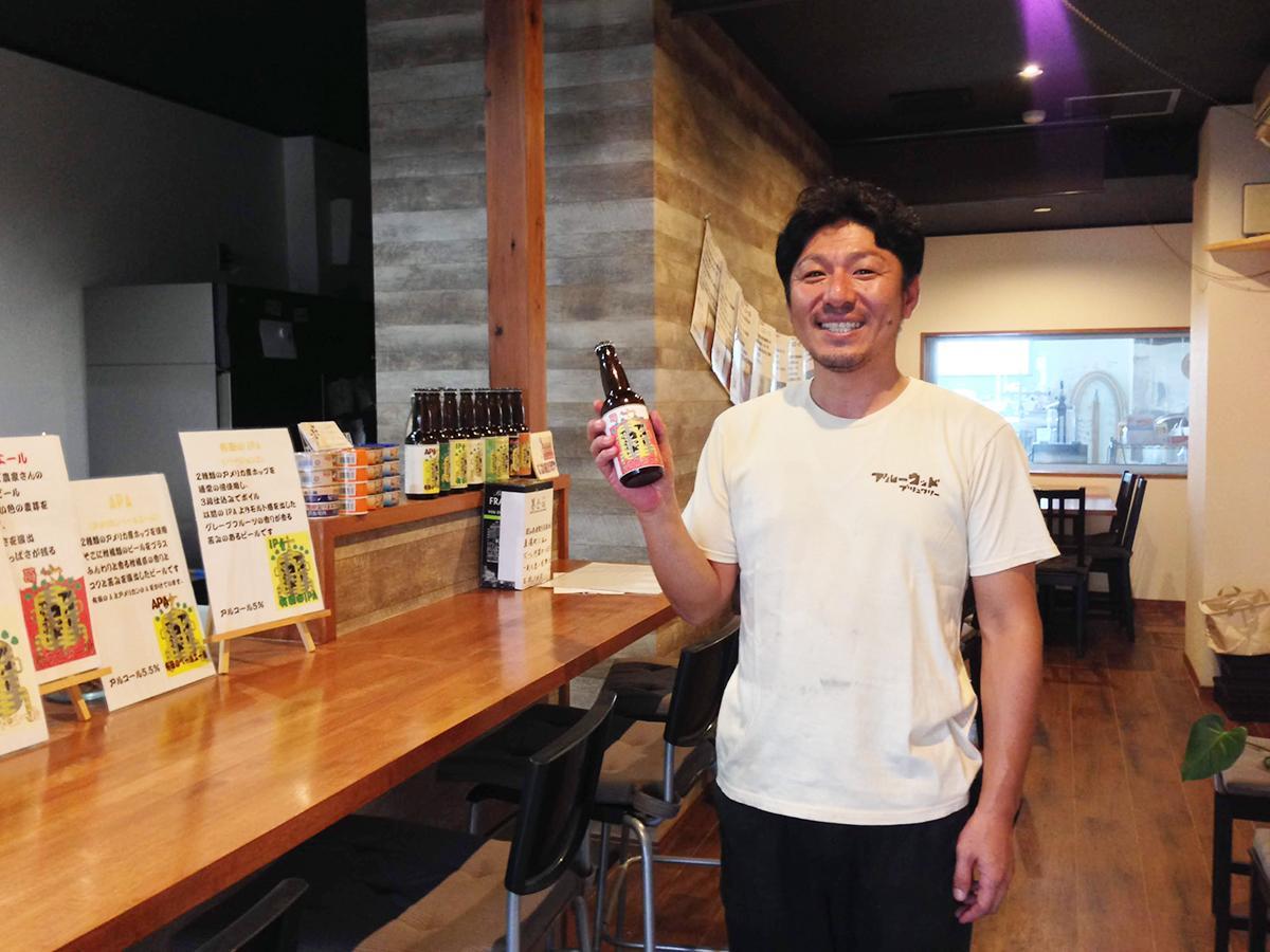 醸造所を併設するパブで自家製ビール「いちごエール」を手にする児島さん