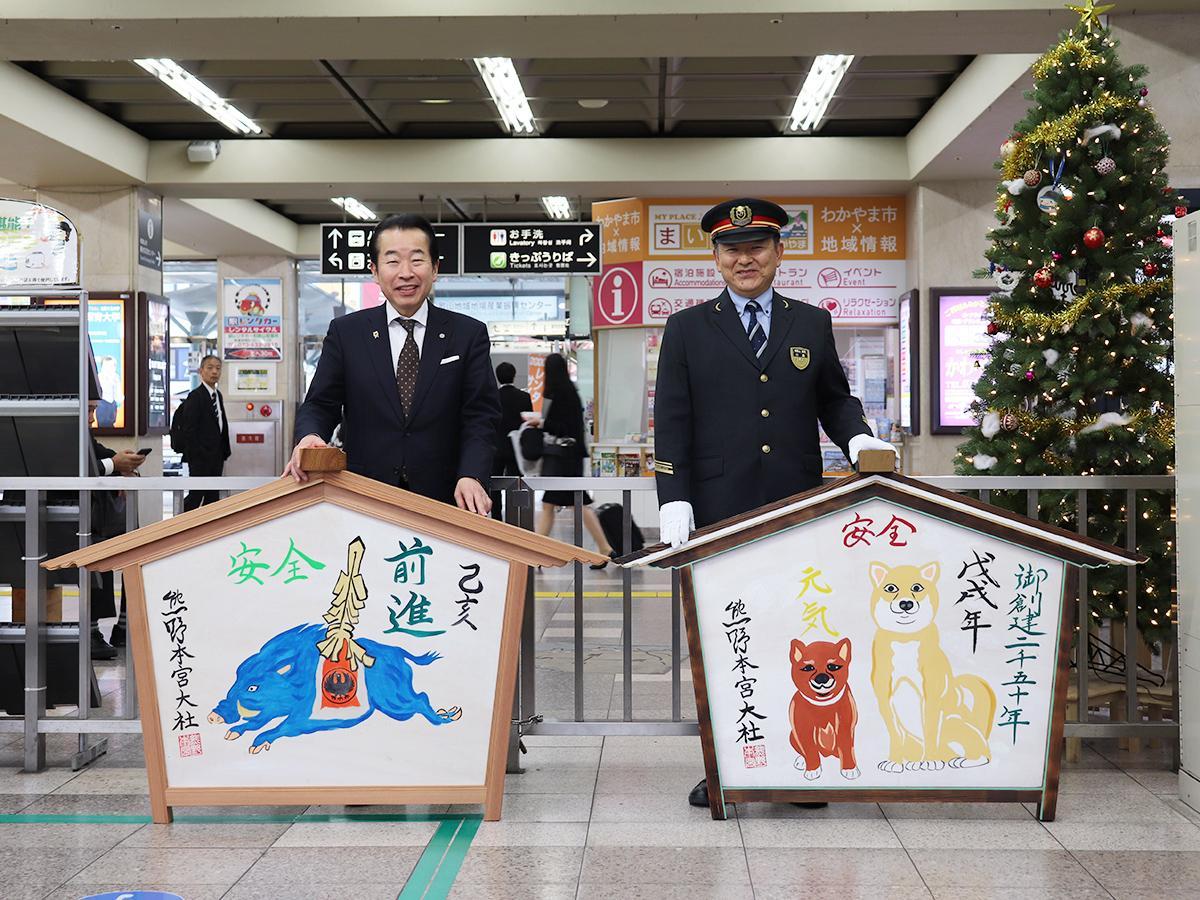 来年のえとが描かれた絵馬を持つ九鬼家隆宮司(左)と今年の絵馬を持つ小島義弘和歌山駅長
