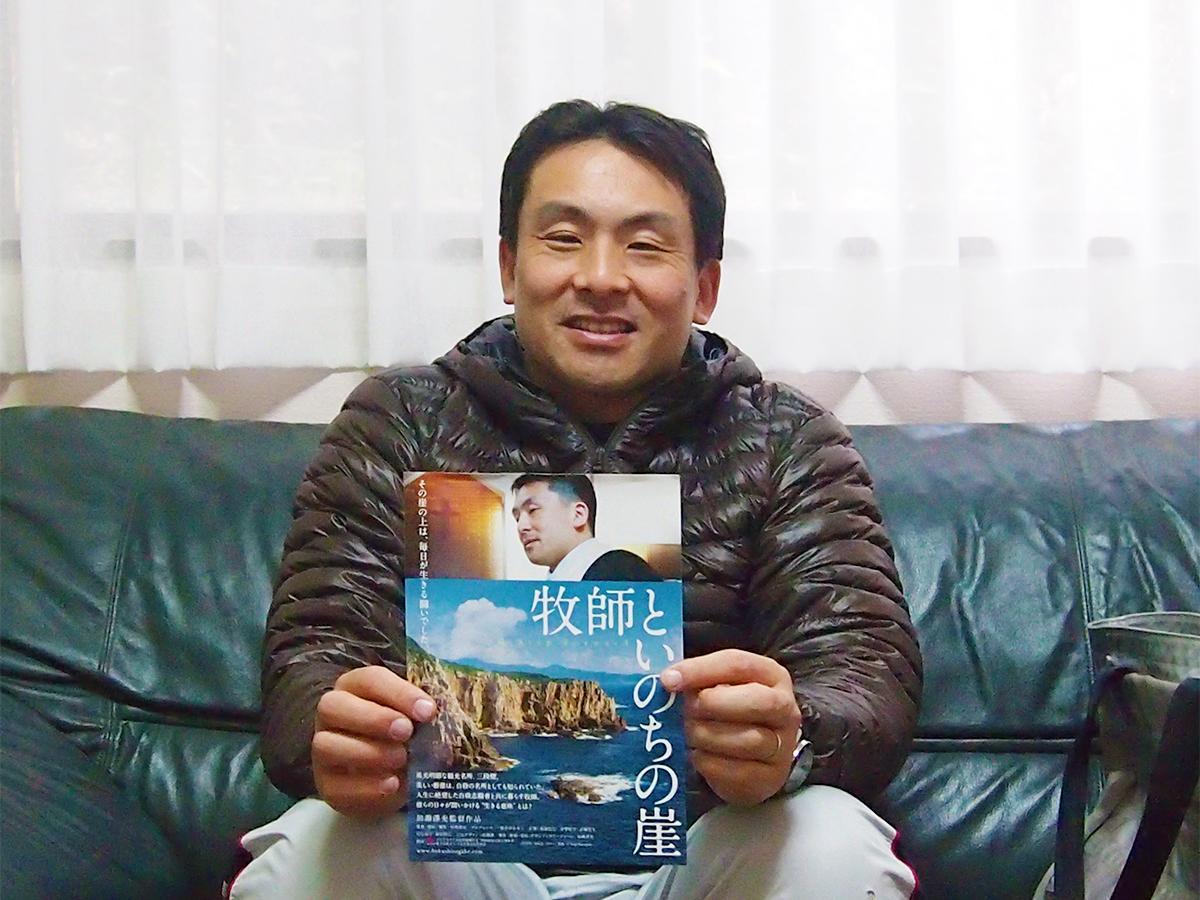 ドキュメンタリー映画「牧師といのちの崖」のチラシを手にする牧師・藤薮庸一さん
