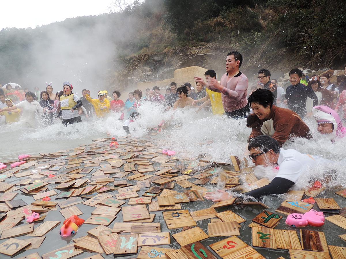 湯船に浮かぶ取り札に向かって飛び込む参加者