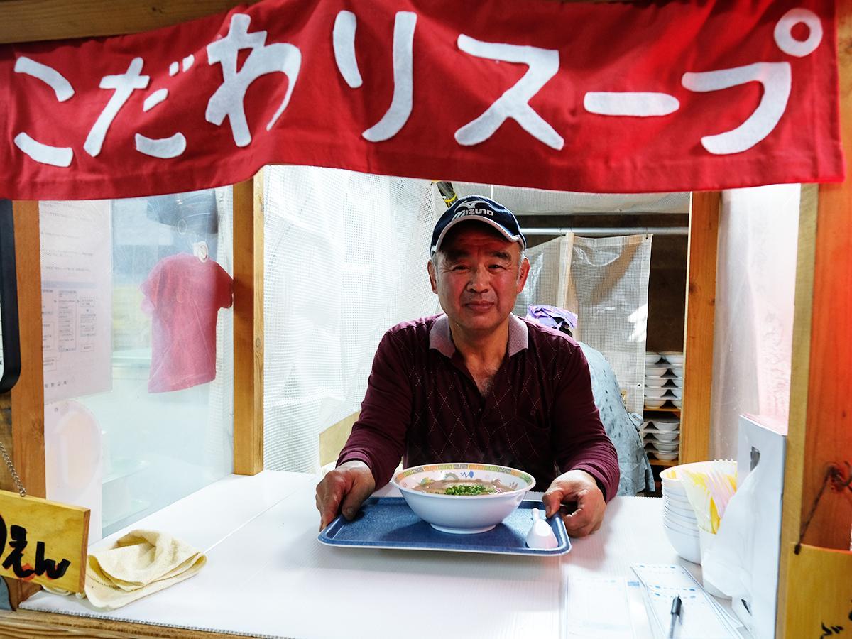 倉庫内の屋台でラーメンを売る店主の平山忠央さん