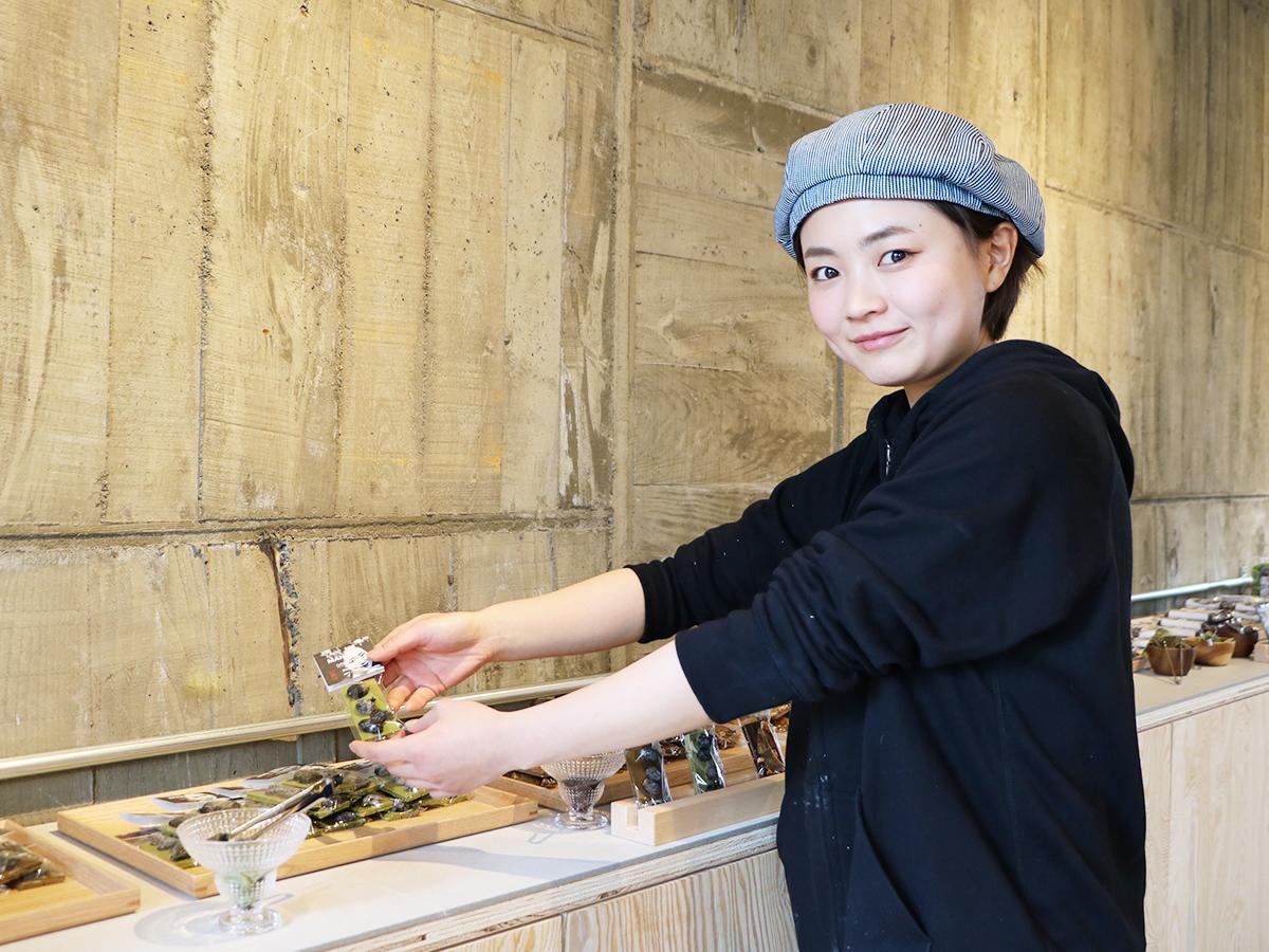 玉林園の抹茶を使ったチョコレートに黒豆を合わせたマンディアンを手にする店長の辻本穂乃華さん