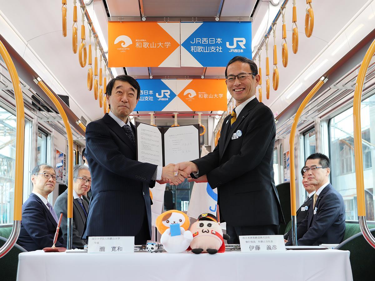 協定書を手にがっちり握手を交わす瀧和歌山大学長(左)と伊藤和歌山支社長