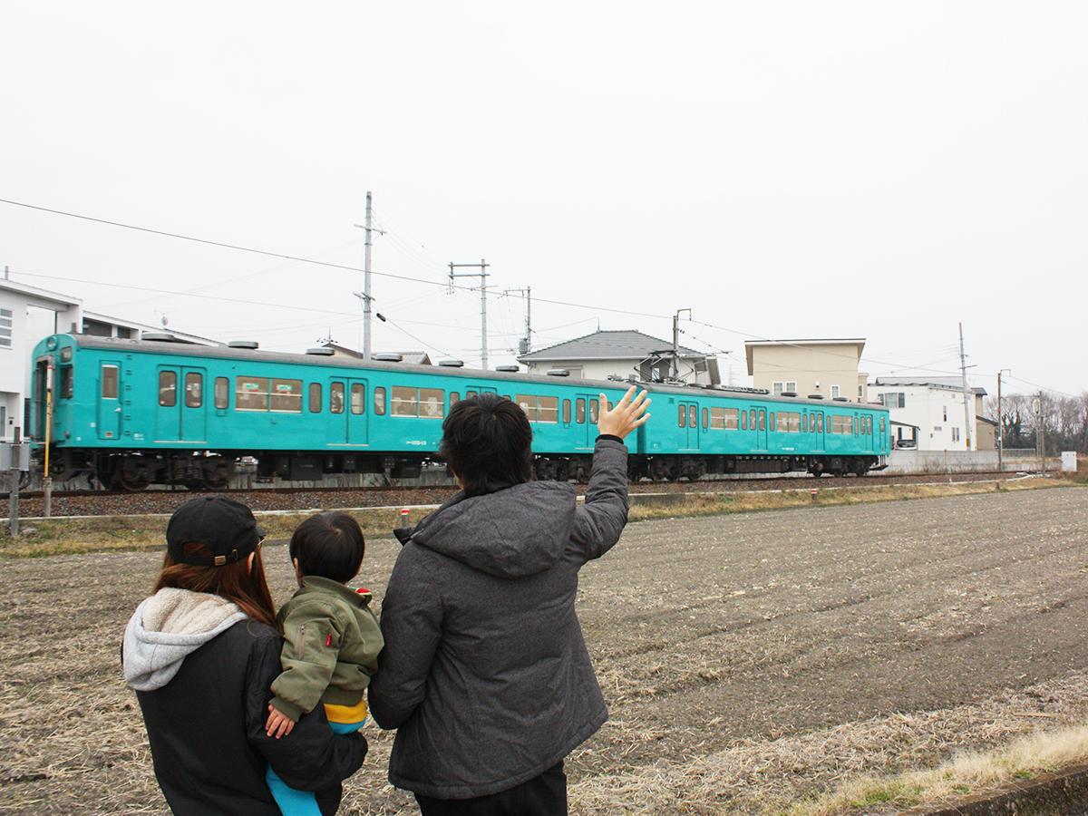 撮影リハーサルで和歌山線沿線で車両に「手を振る」家族(2月16日)