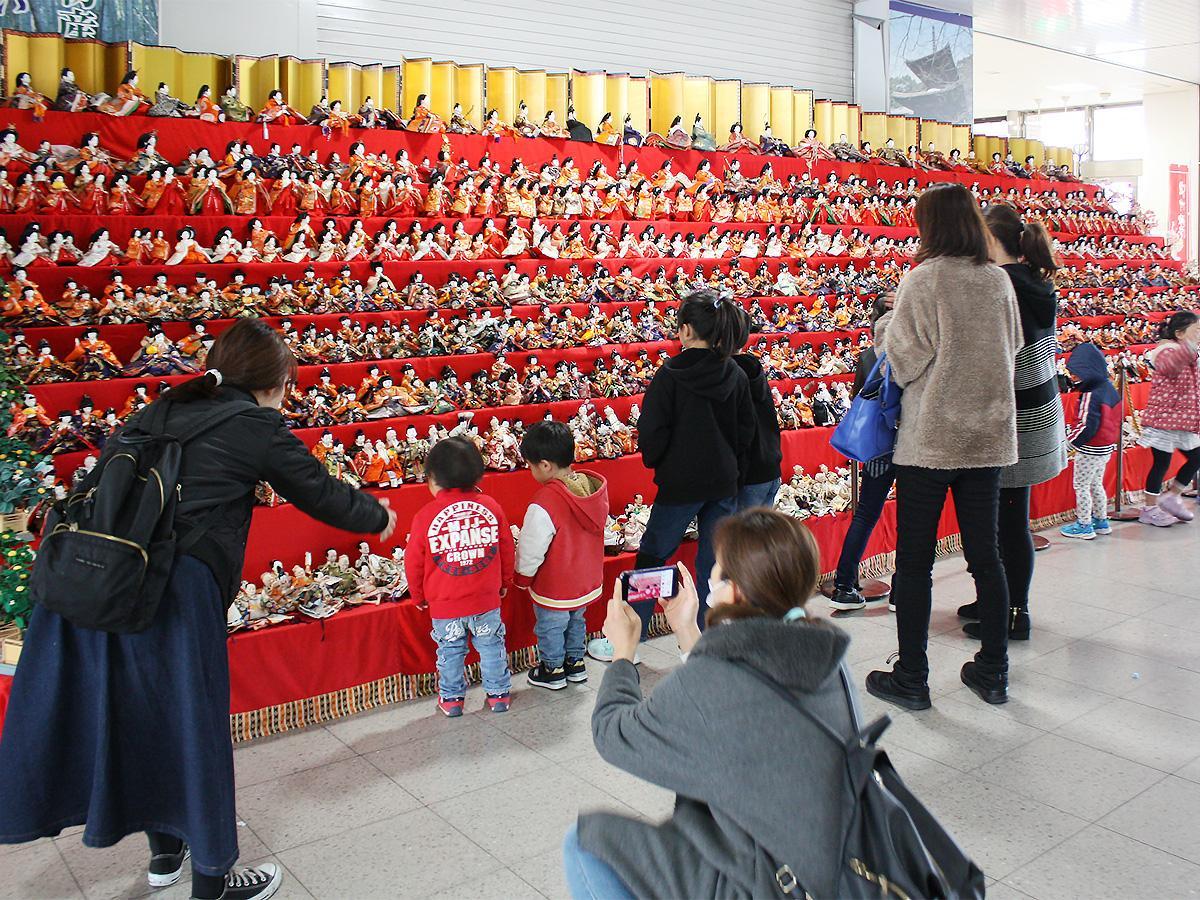 海南駅改札前に展示されている「千体雛」前で親子らが撮影する様子