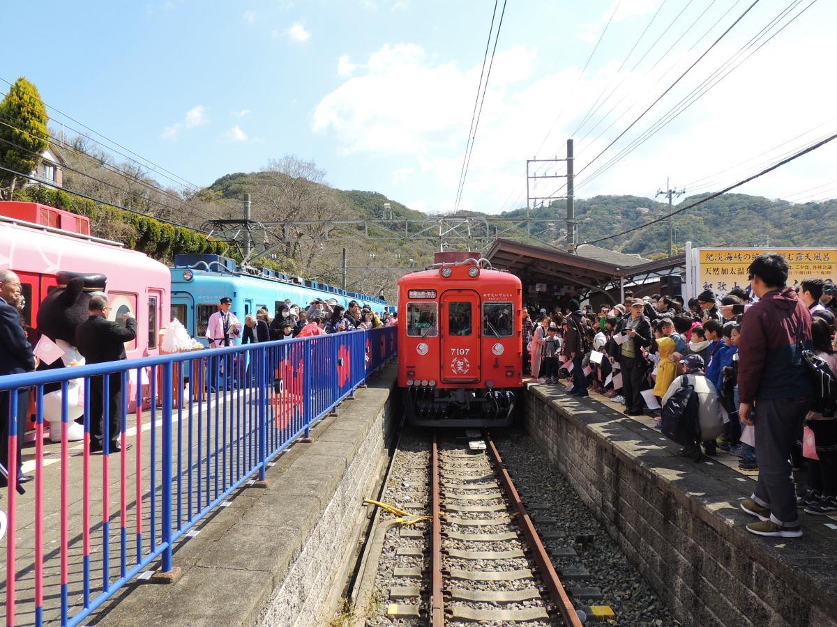 加太駅でフラッグを振って新しい「めでたいでんしゃ」を迎える人たち