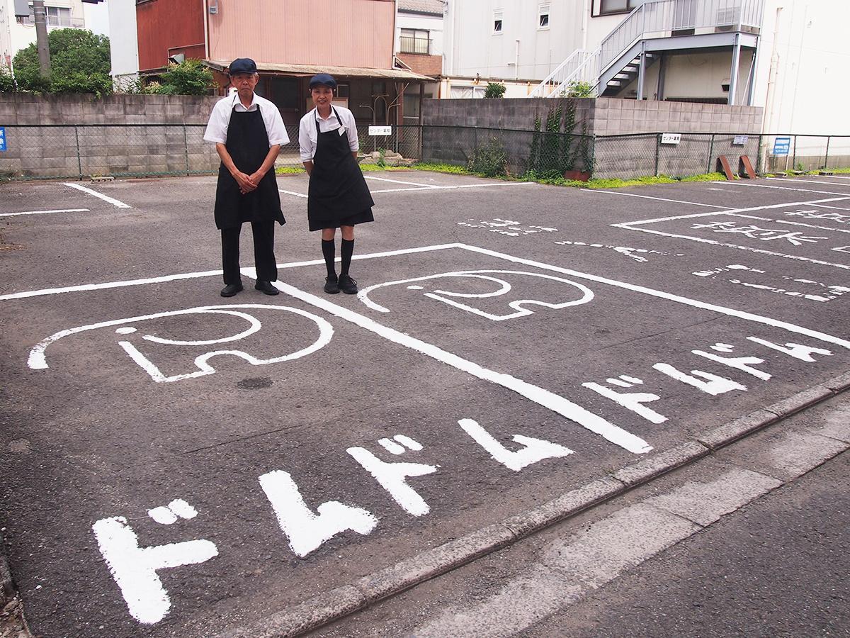 ドムドムハンバーガー海南FC店を経営する上野夫妻と駐車場の「どむぞうくん」標示
