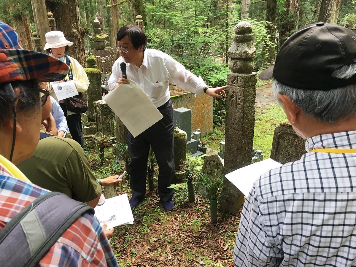 説明を聴きながら鎌倉時代の五輪卒塔婆を見つめる受講生