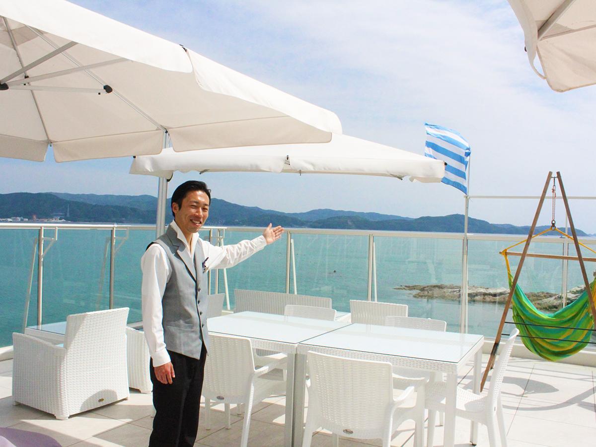 ハンモックとギリシャ国旗を掲げるレストラン直結のテラスと上原さん