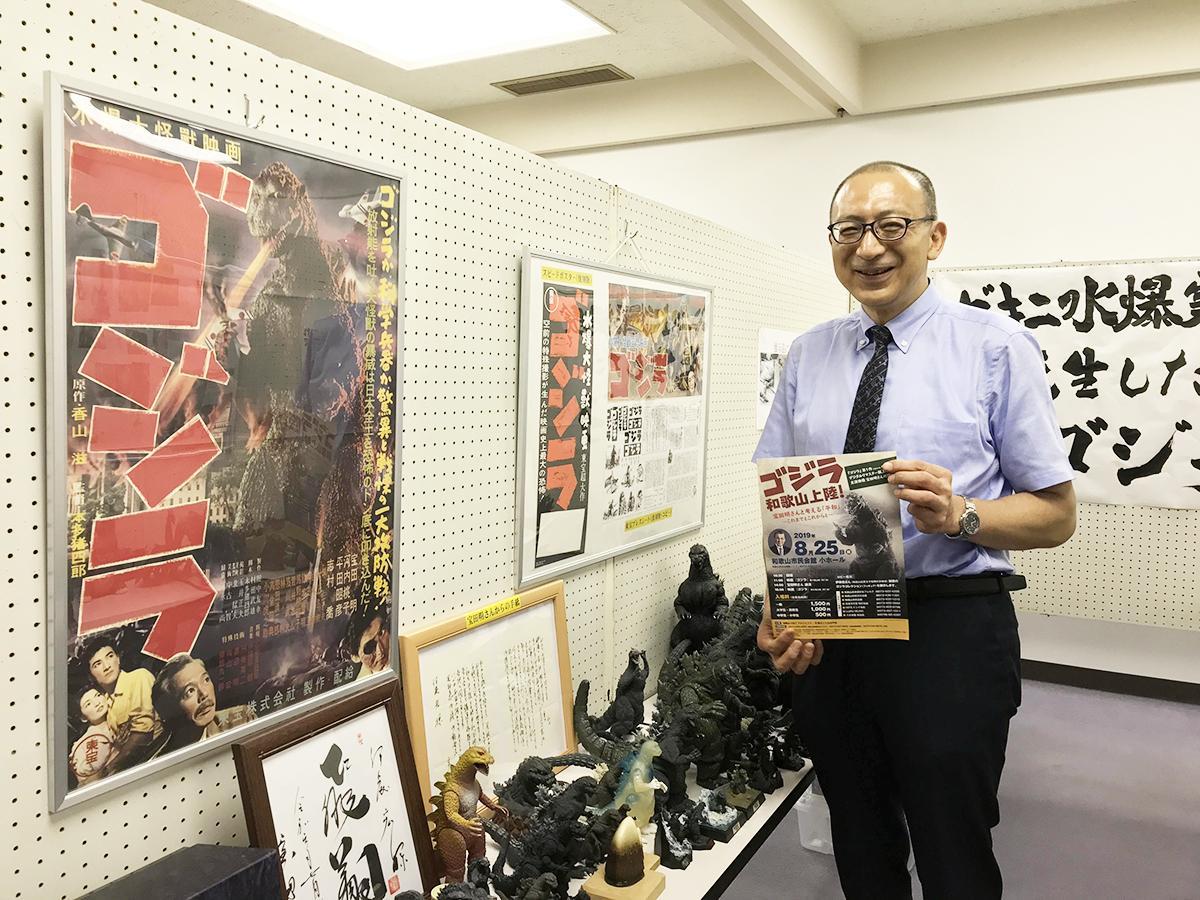 自身のゴジラコレクションの前で参加を呼び掛ける伊藤宏さん