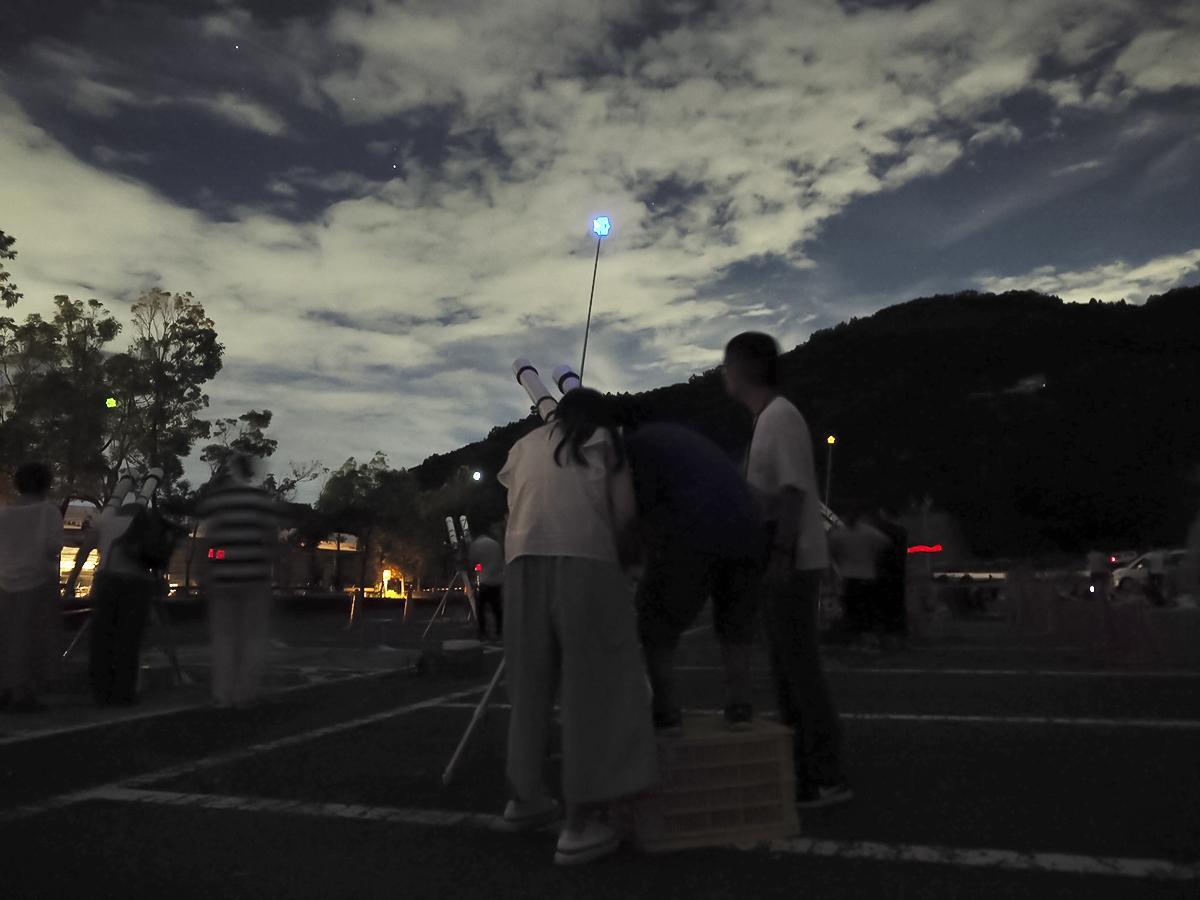 北斗七星の1つ「ミザール」を望遠鏡で覗く参加者たち