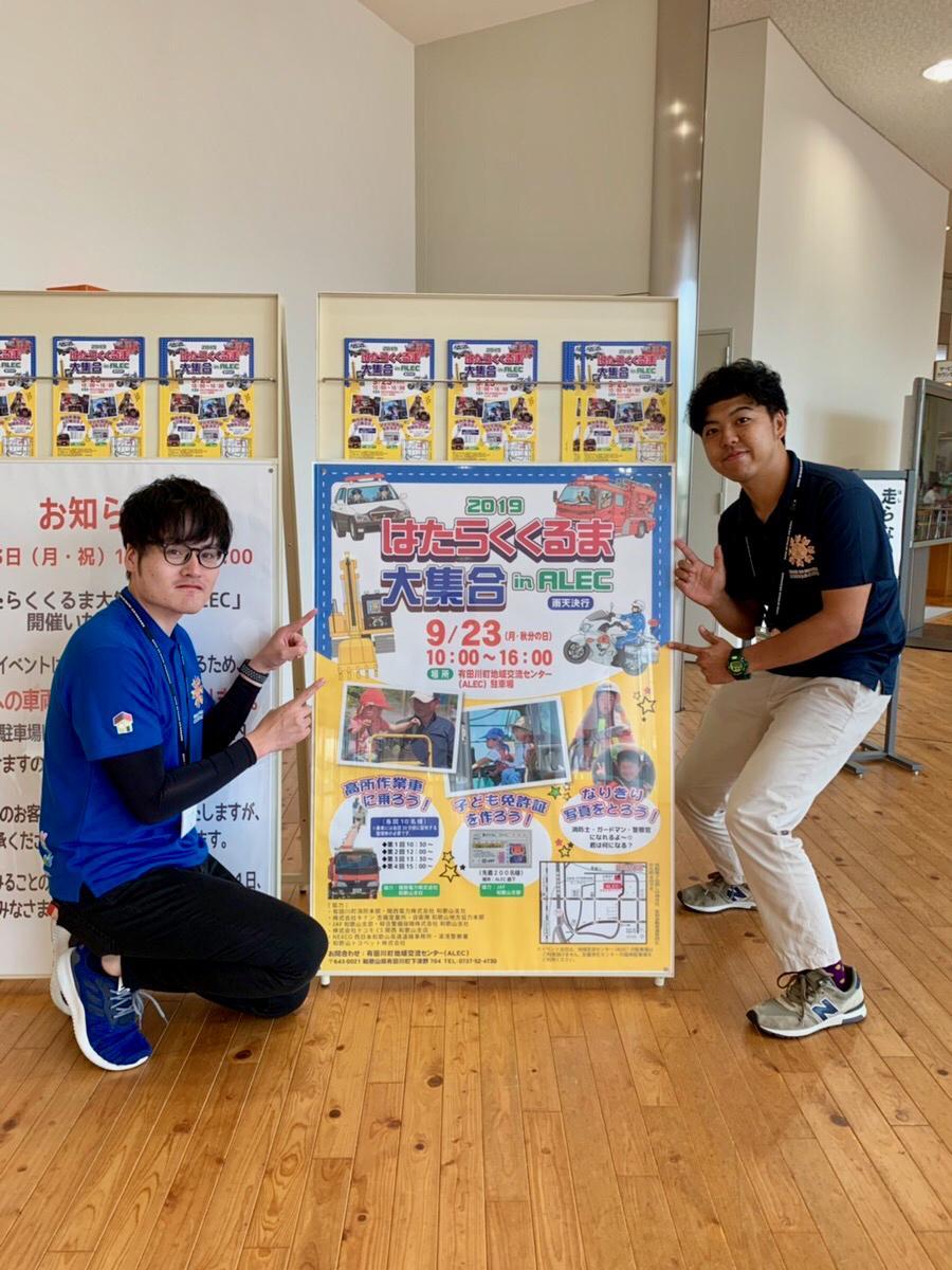 イベントポスターと担当者の門さん(左)