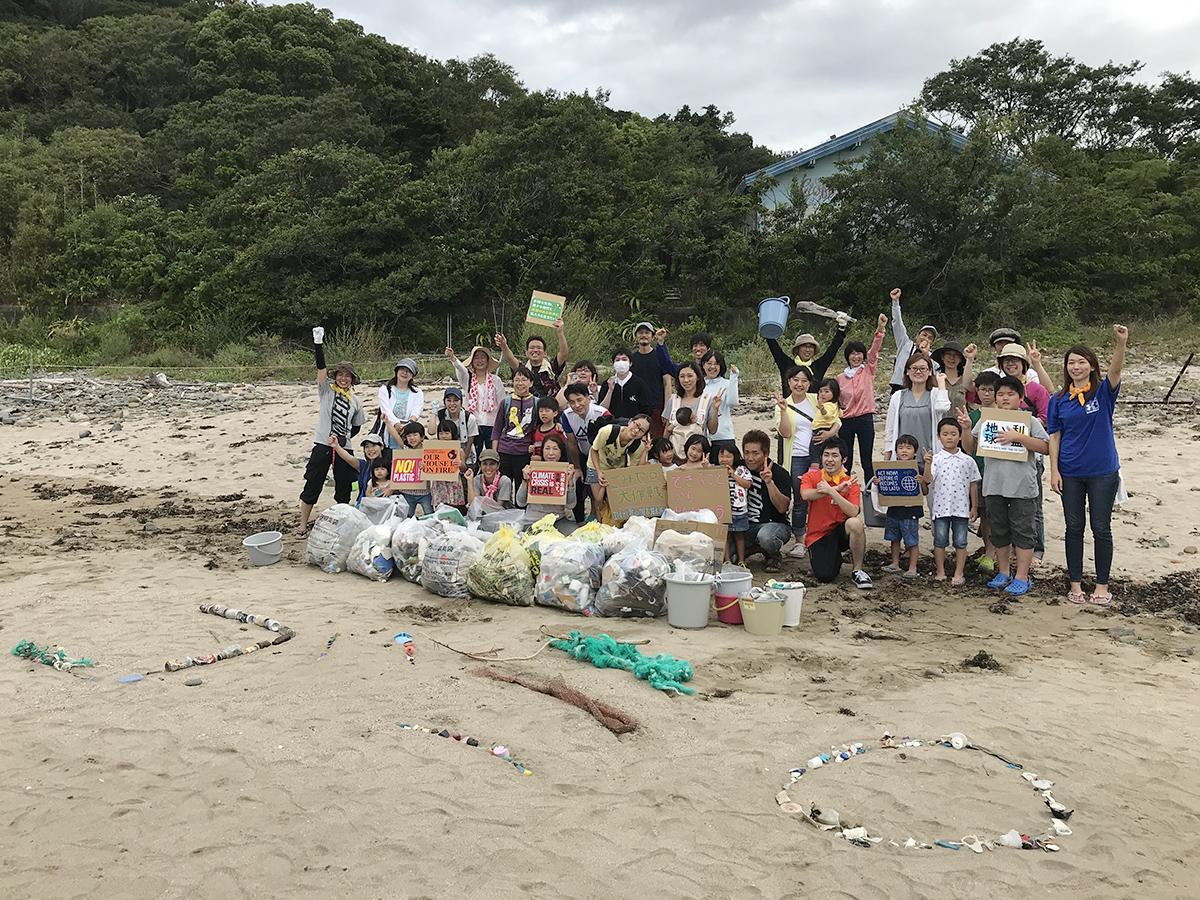 ゴミ拾いの最後に回収したゴミと「ゴミ0」の文字の前で記念撮影する参加者
