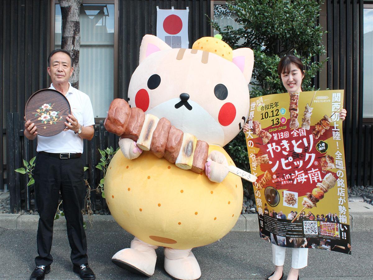 (左から)田村さんと海南市のマスコットキャラクター「海(かい)ニャン」、海南市役所の井村さん
