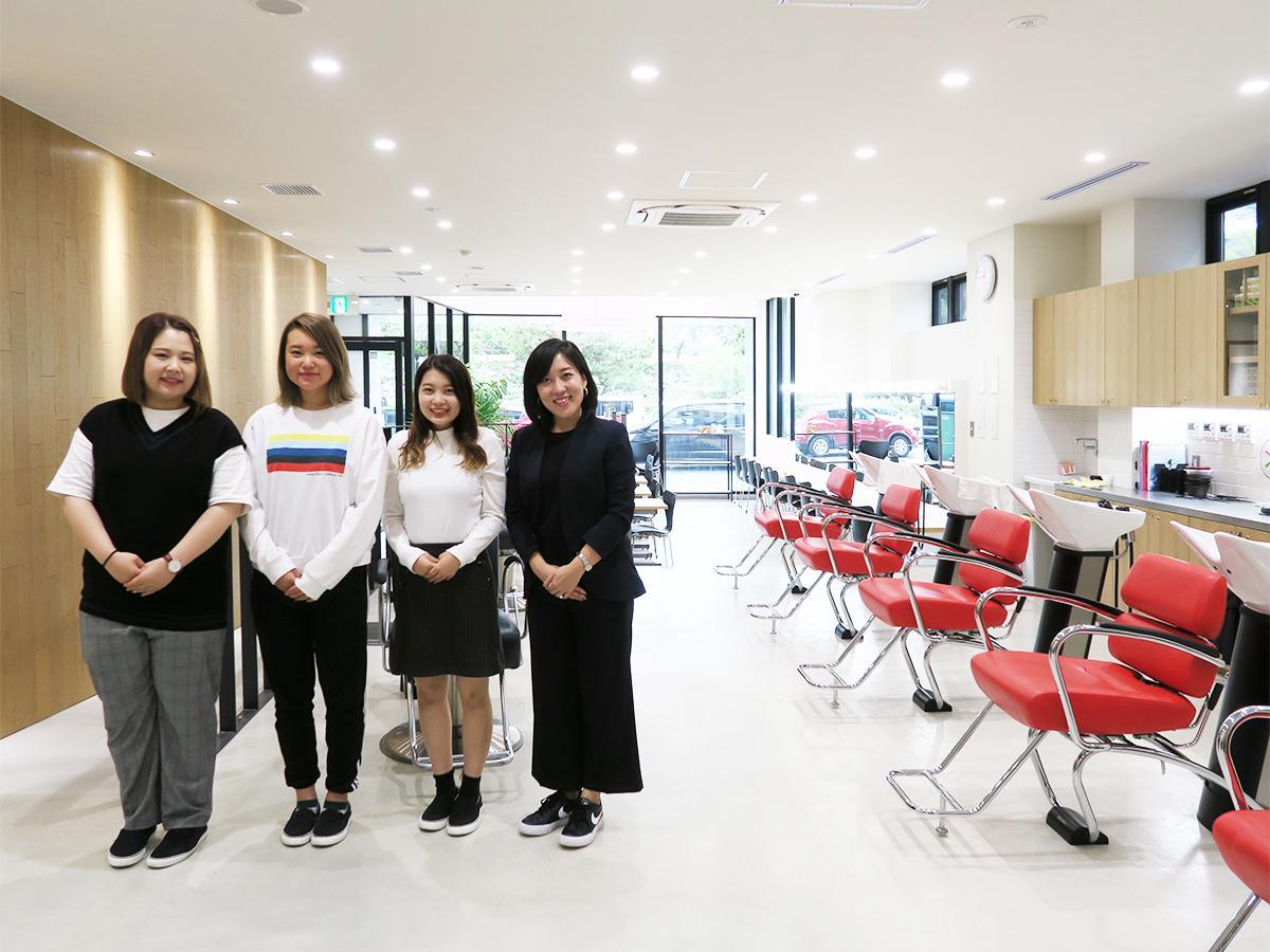 美容室を再現した1階「B-LABO」に立つ、副校長の山本理恵さん(右)と学生たち
