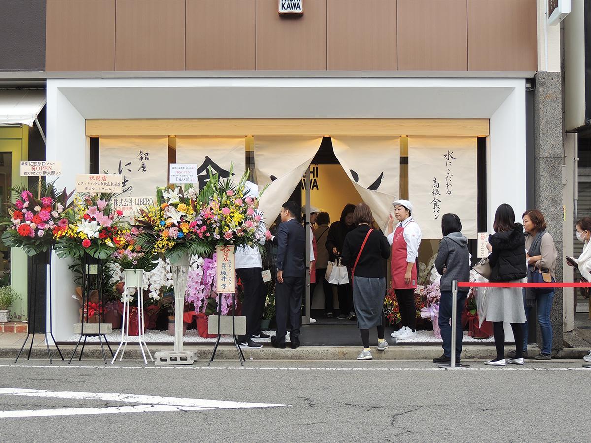開店日に店舗前で行列を作り購入を待つ人々