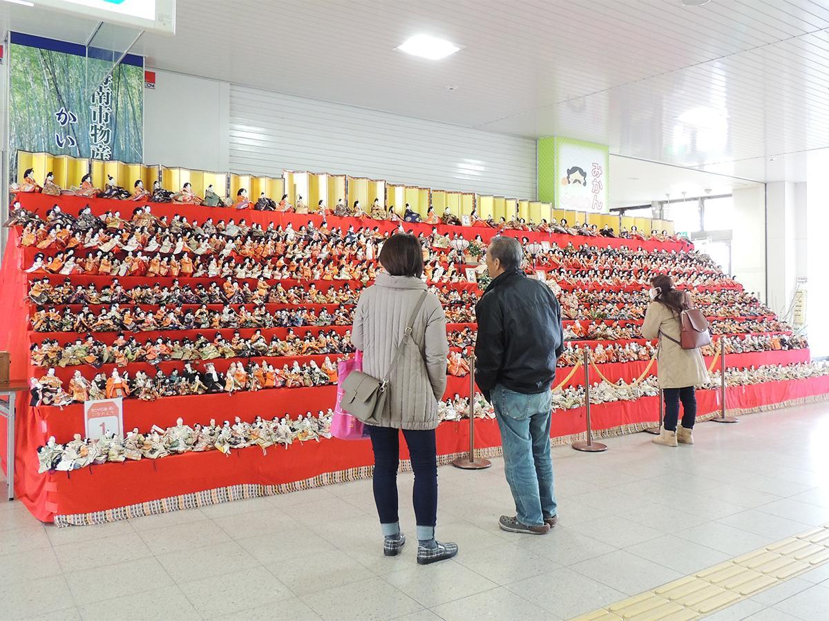 海南駅構内の「千体雛」を眺める通行人たち