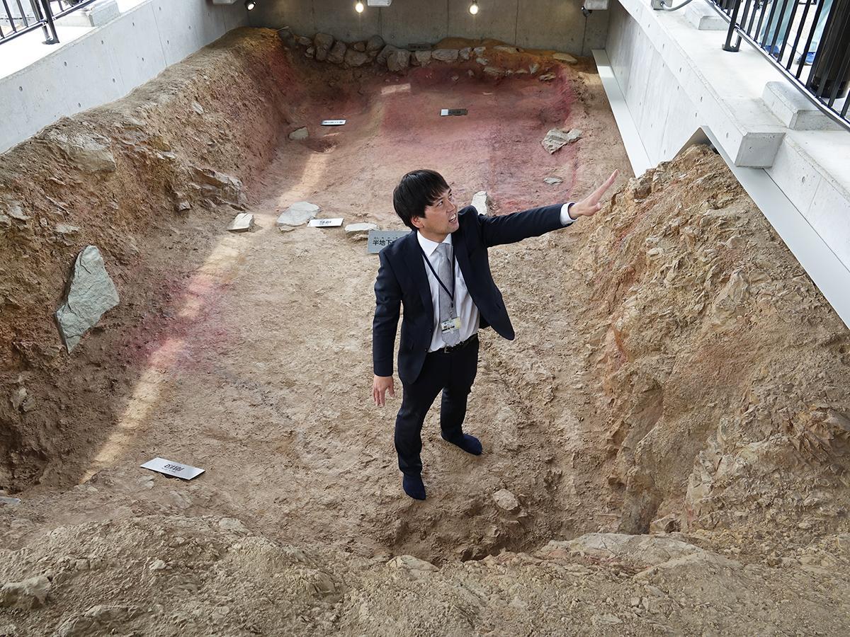 レプリカの半地下式倉庫展示の中で解説する担当者