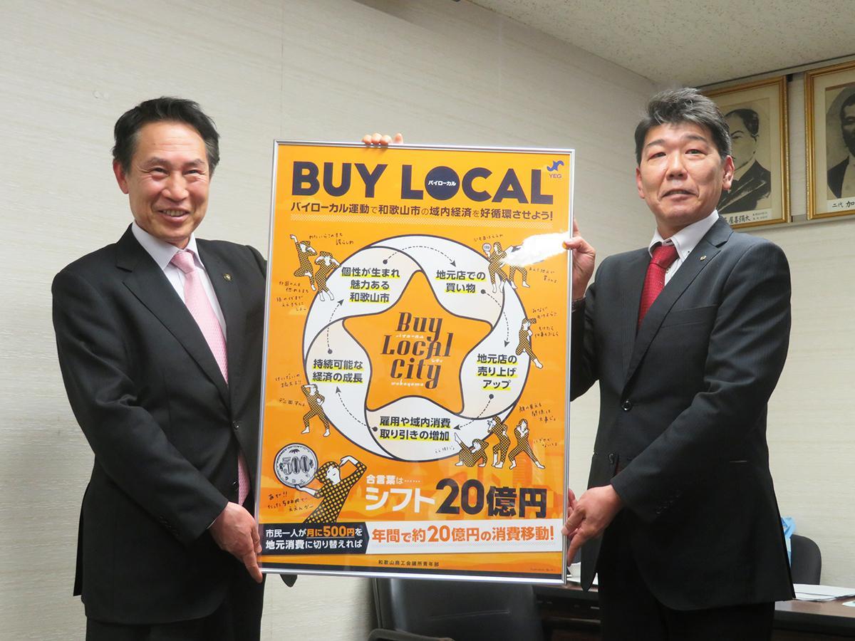 提言を表現したポスターを手にする尾花和歌山市長と和歌山商工会議所青年部の太田さん