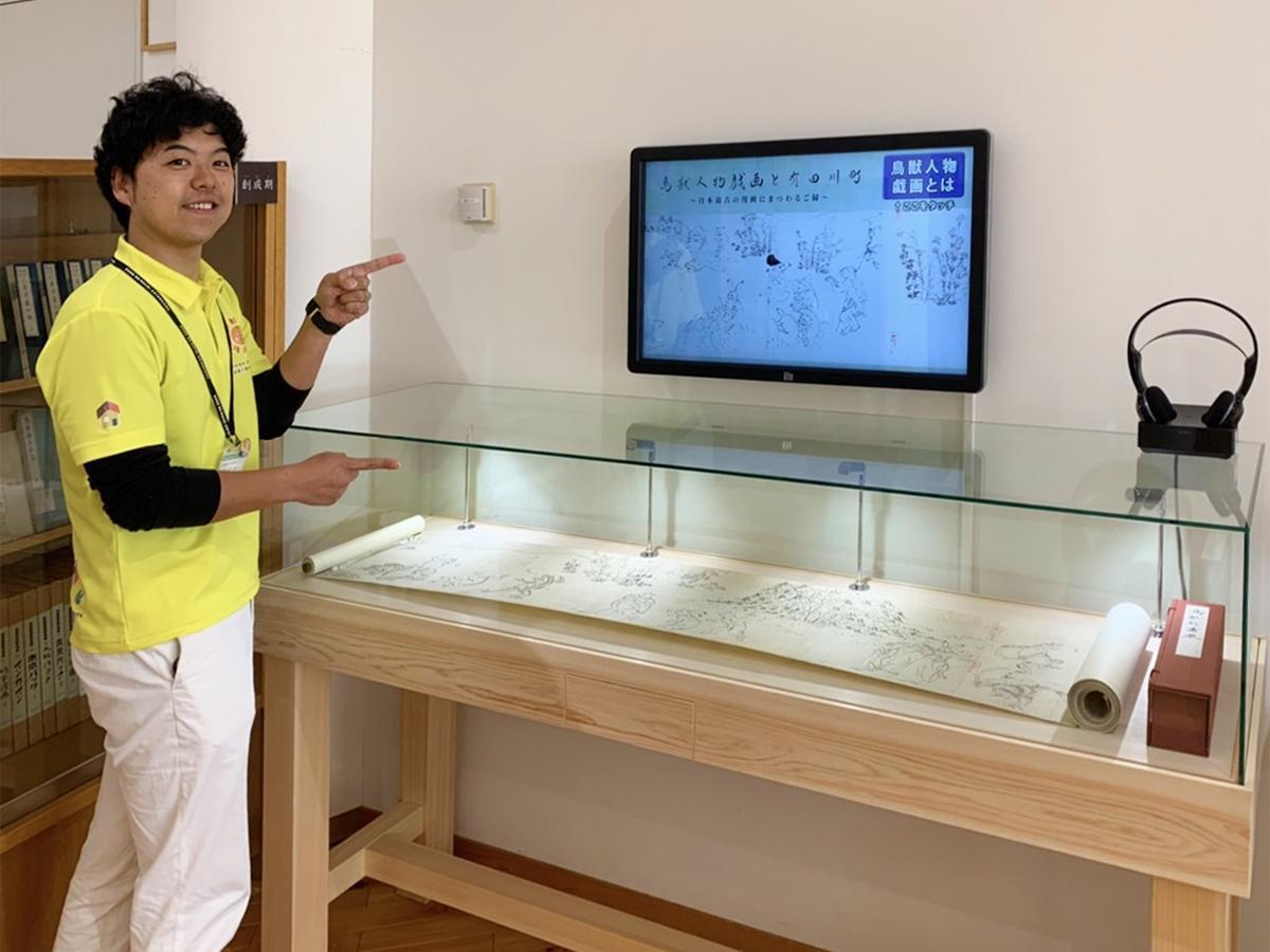 鳥獣人物戯画展示コーナーを紹介する高垣さん