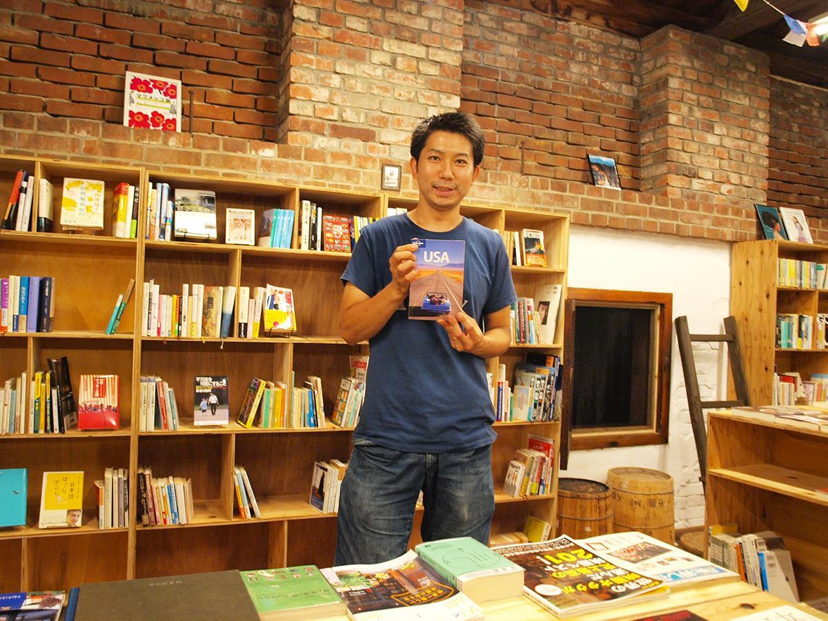 世界の国々をテーマとした書棚の前でアメリカのガイドブックを手にする店主の助野彰昭さん