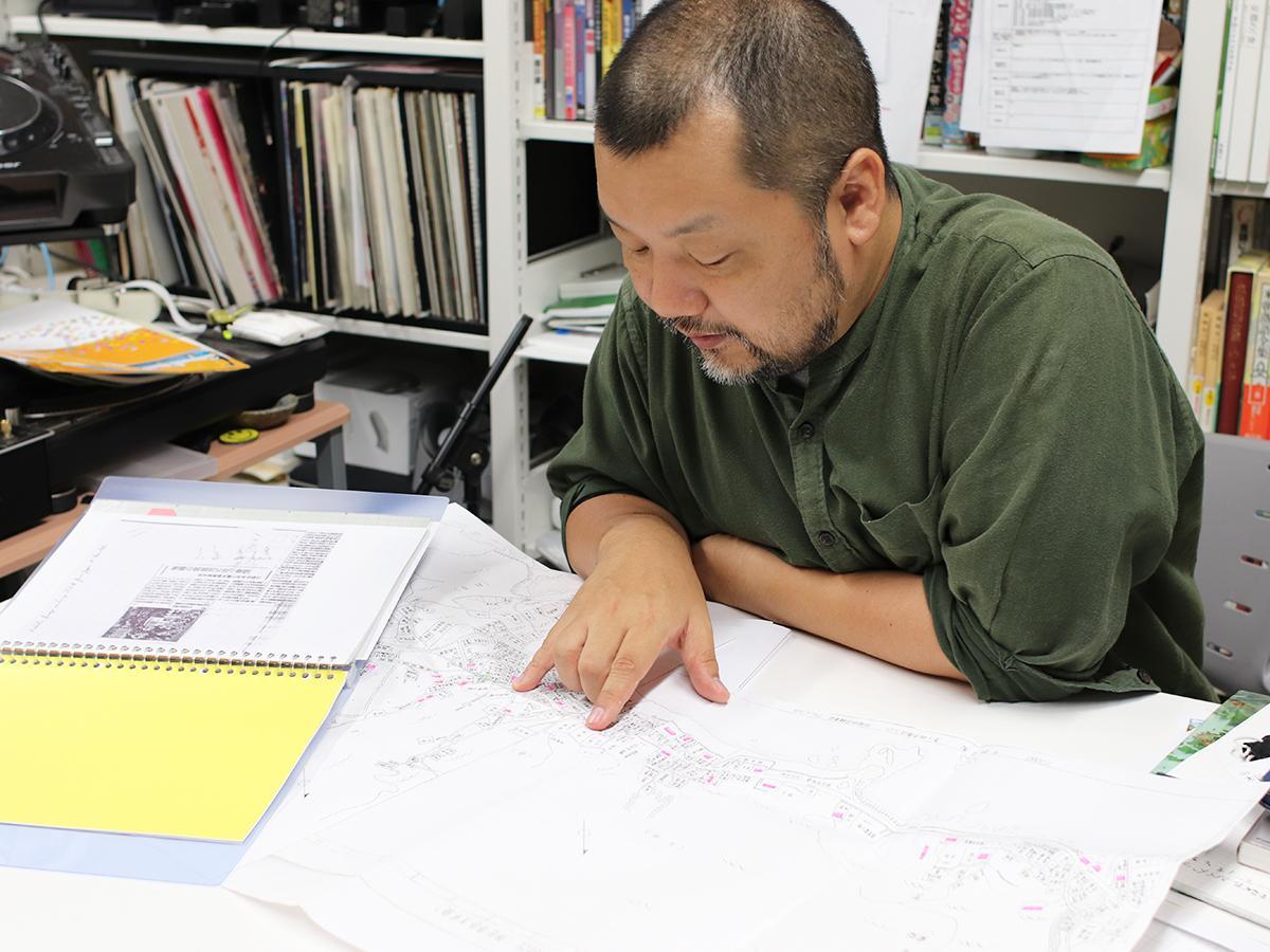 調査した横須賀市秋谷の昔の地図を広げる木川教授
