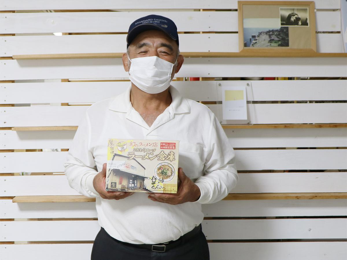 箱入りラーメンを手にする「ラーメン倉庫」の平山さん
