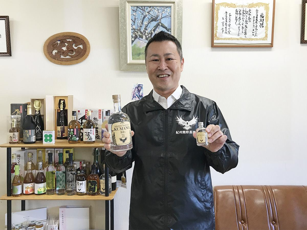 「JAPANESE CRAFT GIN 熊野(熊野ジン)」を手にする長井専務