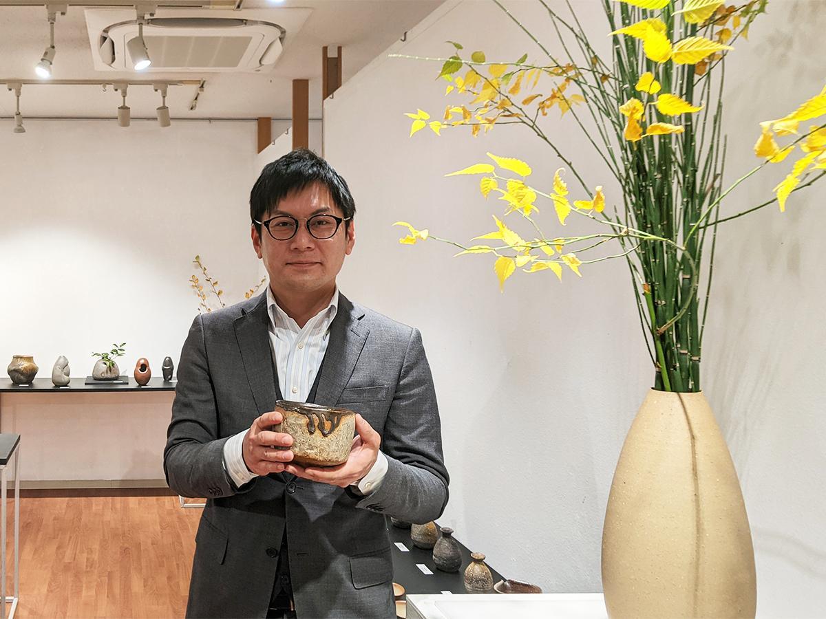 「地層茶碗」を手にする陶芸家の藤田祥さん