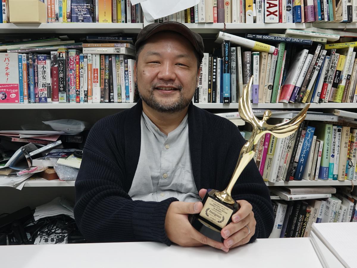 アメリカの国際映画祭で受賞した最優秀長編ドキュメンタリー映画賞のトロフィーを手にする木川剛志さん
