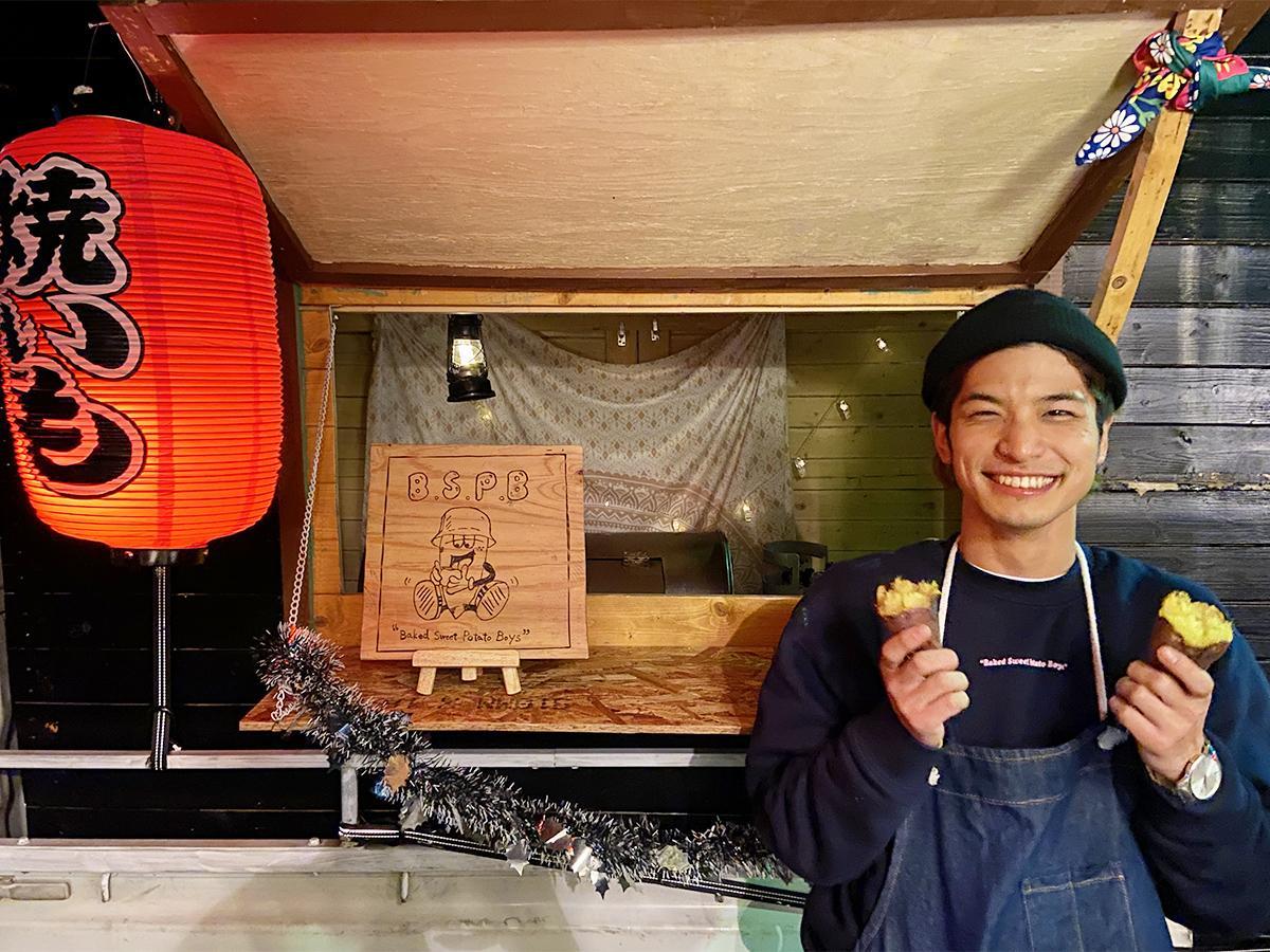 焼き芋を手に持つ店主の前田さん