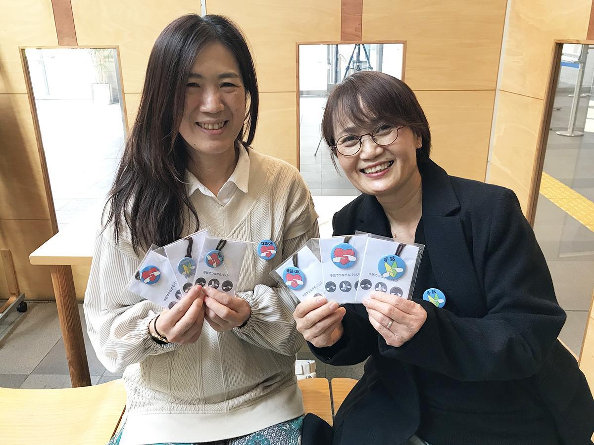 (左から)「手話でつながるバッジ」を手にする、藤本佐知子さんと田中匡子さん