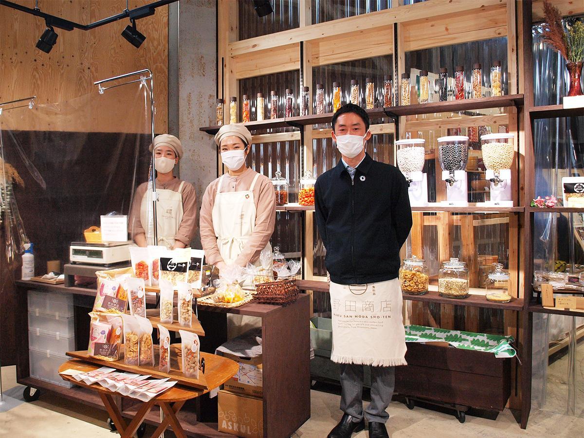 量り売りコーナーの前で野田社長(右)とスタッフ