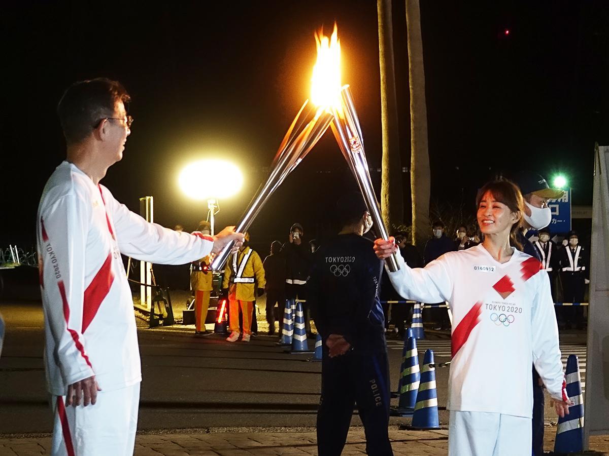 第9区間第11走者からトーチの火を受け取る田中理恵さん(右)