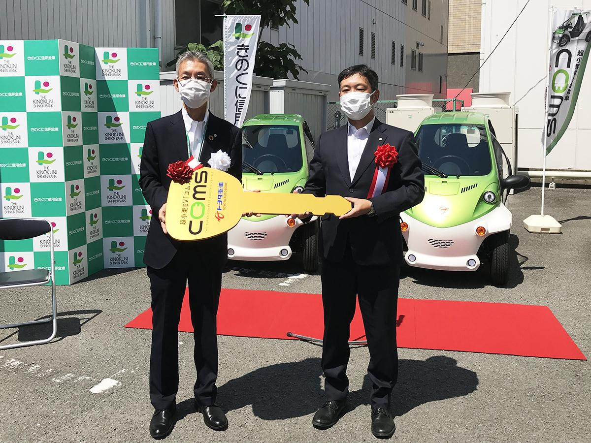 レプリカキーの受け渡しをする、きのくに信用金庫の田谷さん(左)と和歌山トヨタ自動車の山崎さん