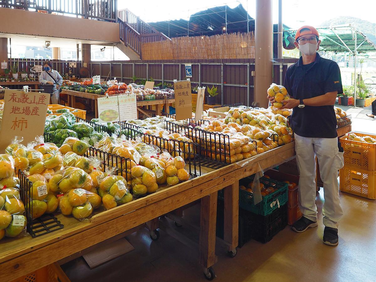 和歌山県産の柿を手にする店長の樋瀬さん