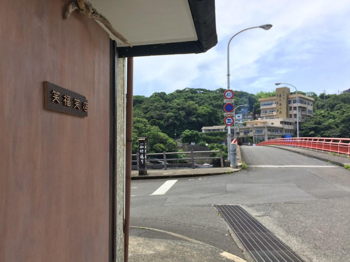朱色の欄干が鮮やかな安房川橋のたもとに立つ「笑福笑店」
