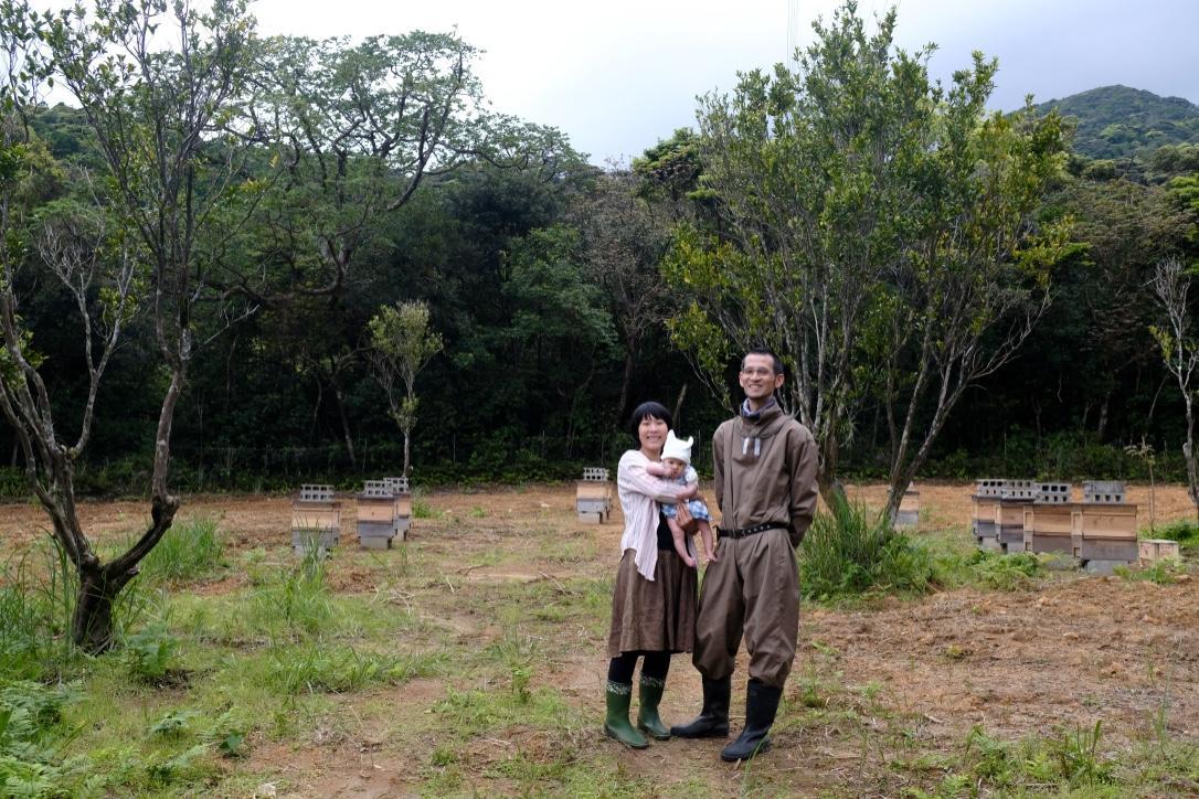 タンカンの木を背景に笑顔を見せる久保さんと家族
